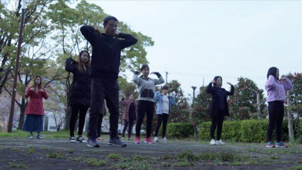 Trabajadoras migrantes en Japón hacen ejercicios matutinos en un parque.