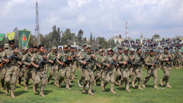 Fighters from the Syrian Kurdish People's Protection Units (YPG) militia take part in a parade in Qamishli, Syria (28 March 2019)