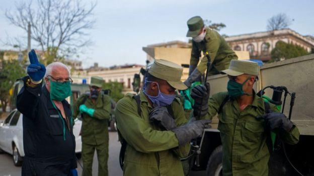 Soldados con mascarillas en La Habana yendo a desinfectar las calles.
