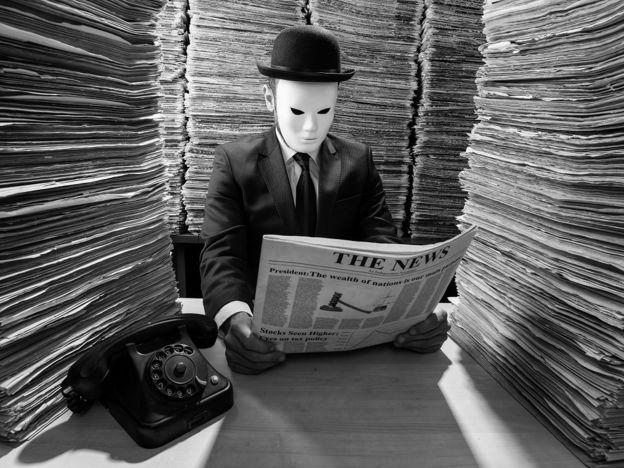 مردی که ماسک به صورت دارد و در حال خواندن روزنامه است