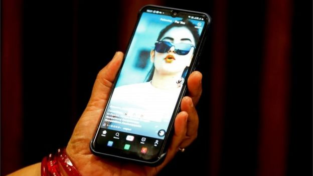 A woman watches a short video on the Chinese video-sharing app TikTok on her smartphone, in Bhopal, central India, 29 June 2020.