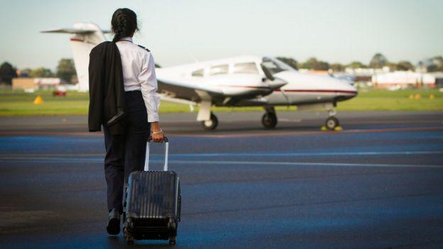 Piloto de avión mujer camina hacia la nave.