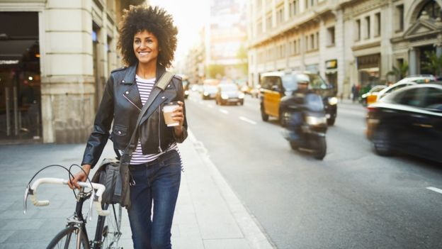 Девушка идет по городу с кофе и велосипедом
