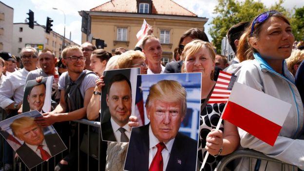 ABD Başkanı Donald Trump ve Polonya Cumhurbaşkanı Andrzej Duda'nın portrelerini çeken insanlar 6 Temmuz'da Varşova'daki Krasinski Meydanı'nda bekliyorlar