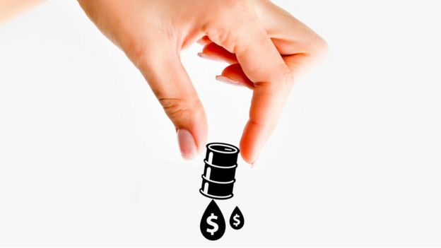 Woman's hand grabbing a barrel of oil with dollar symbol.