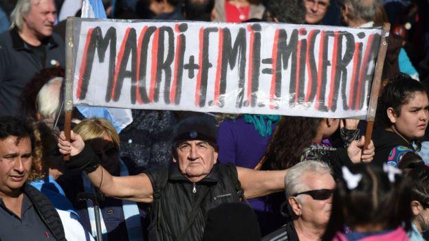 Hombre sostiene un cartel con la leyenda: Macri+FMI=Miseria.