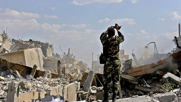 Suriyeli bir asker, ülkesindeki yıkımın fotoğrafını çekiyor