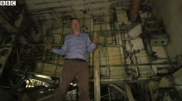 مراسل بي بي سي روب ووكر داخل تجويف عجلات هبوط إحدى الطائرات