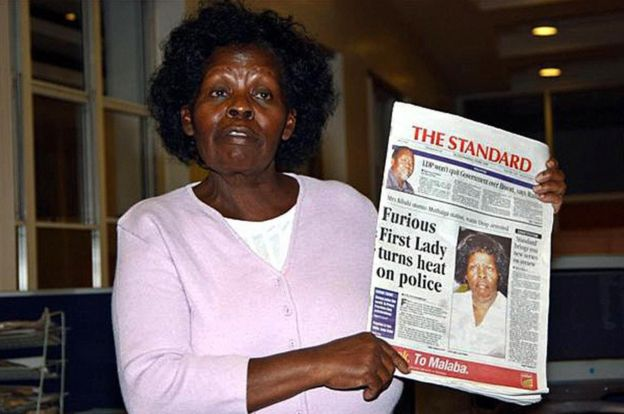 Pictured in May 2005, Kenya's First Lady Lucy Kibaki speaks to the media while holding a copy of a local newspaper with the headline 'Furious First Lady turns heat on police'