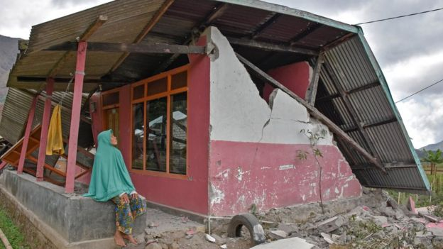 A villager sits at her damaged house after an earthquake hit Sembalun Bumbung village in Lombok Timur, Indonesia, July 29, 2018.