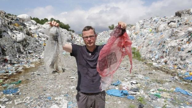 Hugh Fearnley-Whittingstall holding up plastic waste at a dump in Malaysia