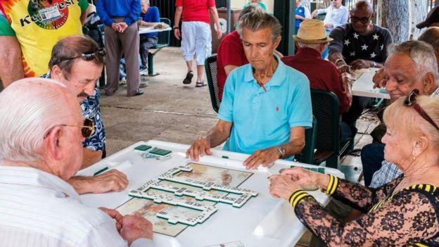 Un grupo de adultos mayores jugando dominó