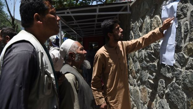 Men check a list of casualties after a car bombing in Kabul, 1 July