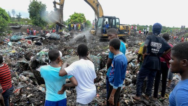 People watch rescuers search for bodies of victims buried under collapsed piles of rubbish in Maputo, Mozambique, 19 February 2018