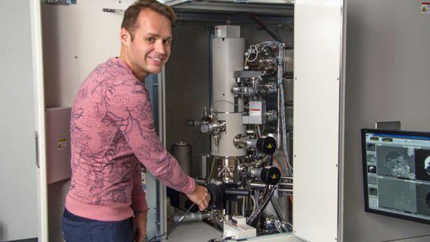 Pierre Haenecour ao lado de um dos microscópios eletrônicos que permitiram analisar o grão de poeira a nível atômico