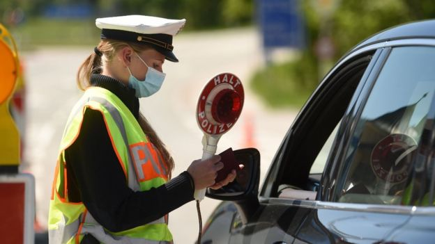 A German police officer wearing a protective mask during a car control at the border crossing between Austria and Germany, near the German village of Oberaudorf