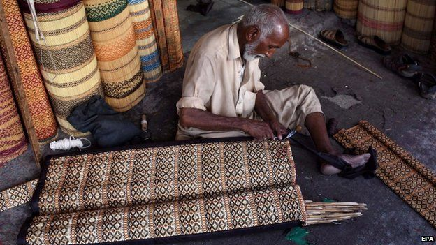 A man makes curtains to offer protection from heat in Karachi