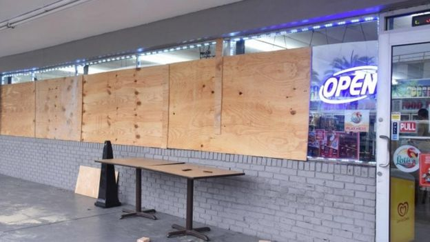 Una tienda con las ventanas tapadas con madera en Miami
