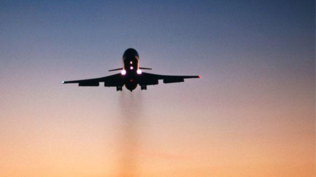 Un avión de pasajeros dejando una estela de humo a su paso.