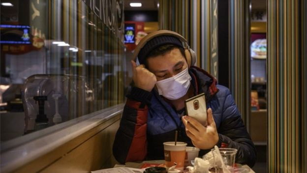 """A man wears a protective mask while eating in a McDonald""""s restaurant in Beijing, China."""