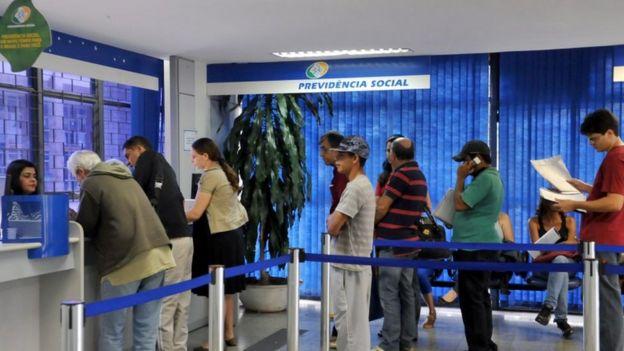 Pessoas em fila dentro de agência do INSS