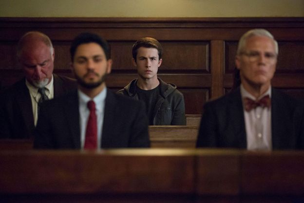 Main character Clay Jensen sits in a courtroom