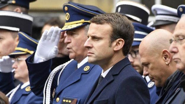 French presidential election candidate for the En Marche movement, Emmanuel Macron (C), attends a ceremony honouring the policeman killed by a jihadist in an attack on the Champs Elysees, on 25 April 2017 at the Paris prefecture building