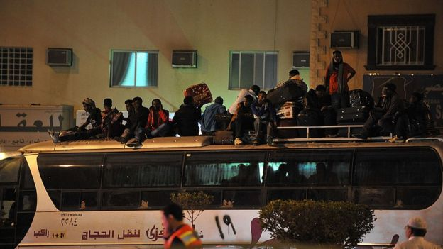 Illegal migrants sit on the roof of a police bus with their belongings on November 13, 2013 before being transferred to a center in the capital Riyadh ahead of their deportatio