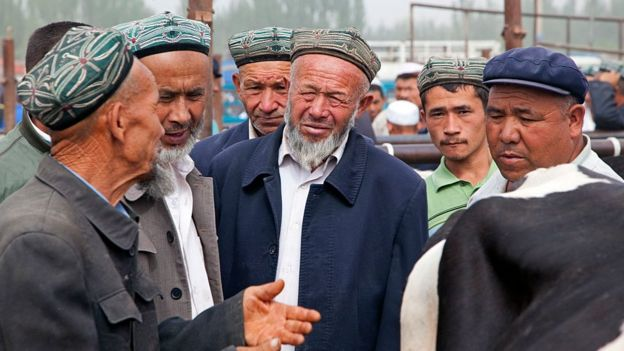 Uyghur farmers wearing doppas, trading cows at the cattle market in Kashgar