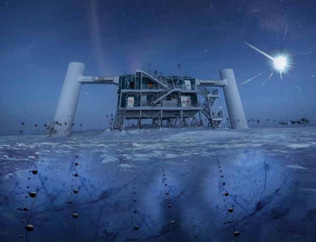 The IceCube facility, a structure built atop the ice in Antarctica. The picture is taken at nighttime, the moon a bright glow in the sky