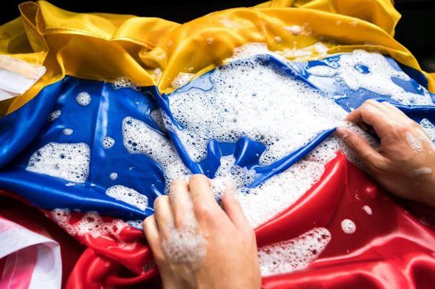 Manos lavando una bandera colombiana.