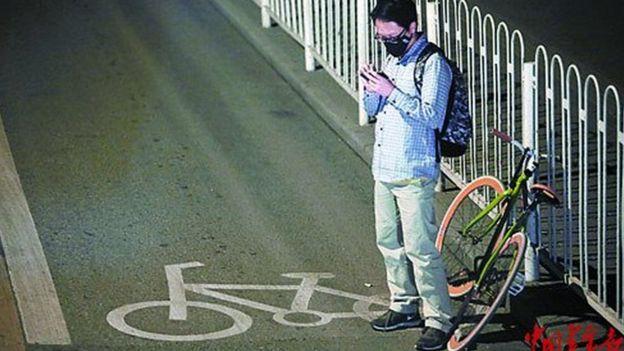Un cycliste vérifie son téléphone portable sur la route aux heures de pointe du soir.