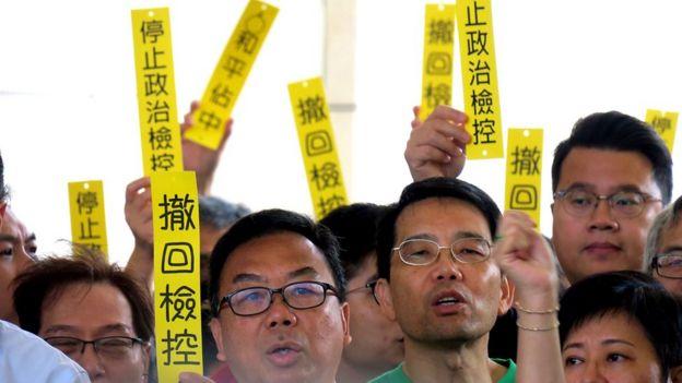 """""""伞运九子""""支持者在法院外举起""""撤回检控""""等标语牌(19/11/2018)"""