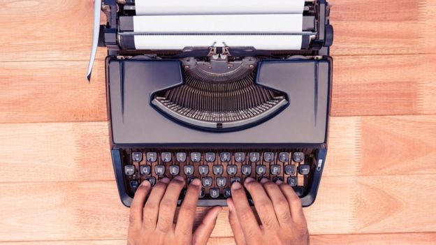 Máquina de escribir antigua con dos manos.