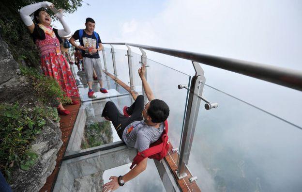 Pessoas fazendo fotos em passarela de cristal