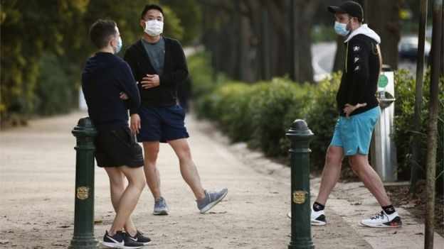 Tres hombres con mascarilla en Melbourne