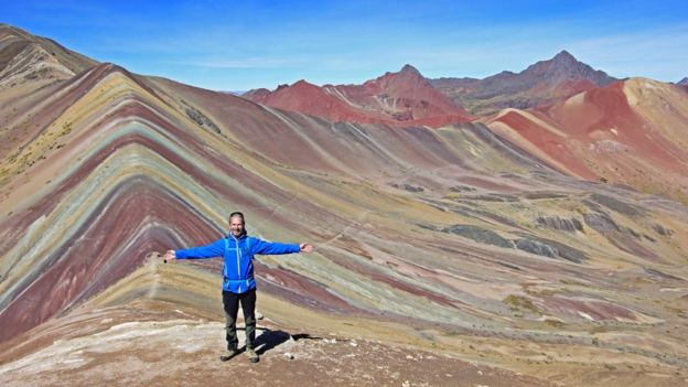 Tourist standing with his back to the Mountain of the Seven Colors.