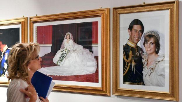 Mujer mira imágenes del casamiento de Carlos y Diana.