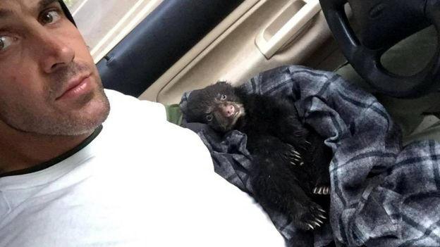 Corey culla l'orso tra le sue braccia avvolta in camicia seduto nella sua auto