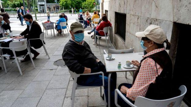 Pessoas com máscara tomando café