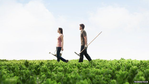 A man and woman walk through a field with gardening equipment