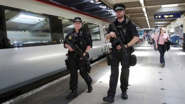 Armed British Transport Police Specialist Operations officers on the platform before boarding a Virgin train to Birmingham New Street at Euston station in London