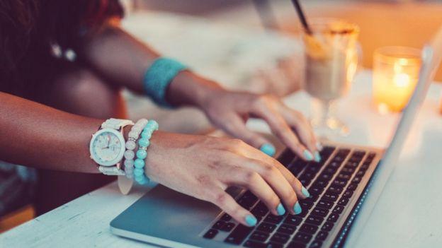 manos de mujer en teclado de computadora.