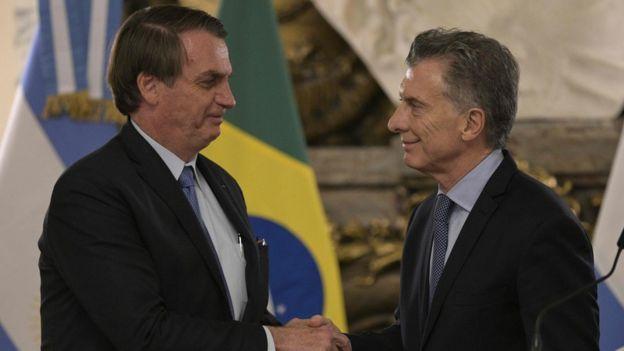 Bolsonaro e Macri apertam as mãos e sorriem, com bandeiras do Brasil e Argentina no plano de fundo
