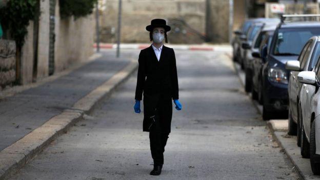Niño ultraortodoxo con mascarilla y guantes en Jerusalén.