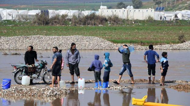 Suriyeliler şiddetli yağmurlardan sonra Afrin yakınlarındaki Deir Balut kampında temiz su bulmaya çalışıyor (11 Şubat 2019)