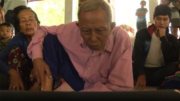 I Nengah Nese mira imágenes de archivo de la erupción de 1963 en una laptop.