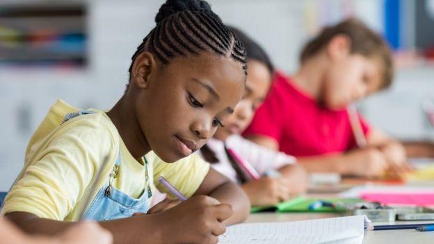 Menina escreve anotações no caderno em sala de aula