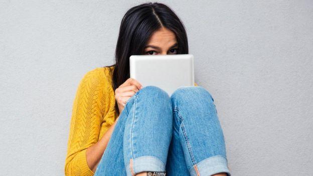 Una mujer escondida tras una tableta