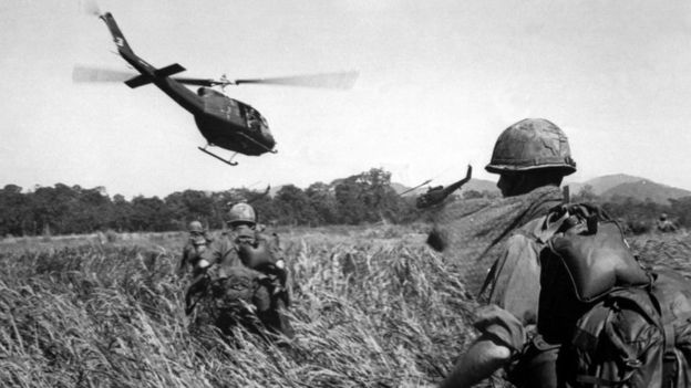 Soldiers on the ground walk through a field while helicopters fly overhead